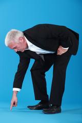 mature businessman pointing et something on floor