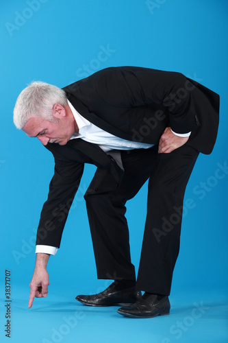 mature businessman pointing et something on floor