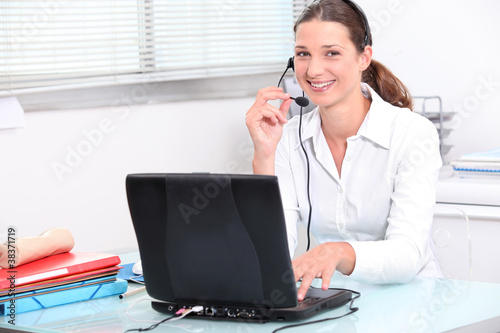 Young woman using a laptop computer and telephone headset