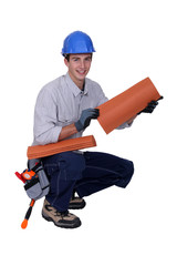 craftsman holding roof tiles