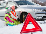 Winter, woman with child putting snow chains onto tyre of car