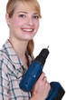Blond woman holding cordless drill