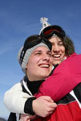Young couple laughing on the ski slopes