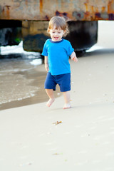 Little boy running on the beach of sea