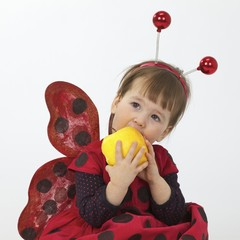 The little girl in a ladybird suit eating an apple