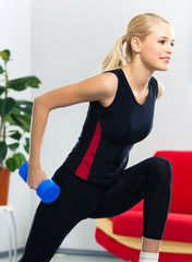 Woman exercising with dumbbell, at home