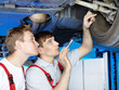Motor mechanic and apprentice inspecting the engine of a car