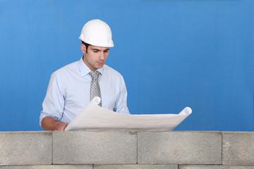Engineer inspecting a construction blueprint