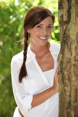 Smiling woman with plaited hair posing next to a tree