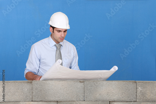 Engineer inspecting a construction blueprint