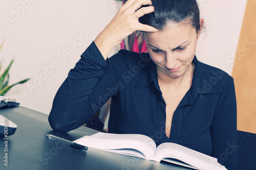 Stressed young woman sitting at a table