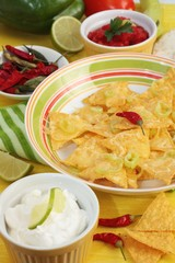 Bowl of nachos with dips including sour cream and salsa