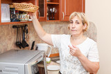 Mature woman standing in kitchen with breadbasket