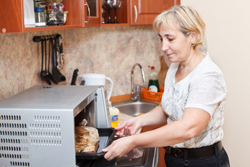 Mature woman standing in kitchen near opened stove