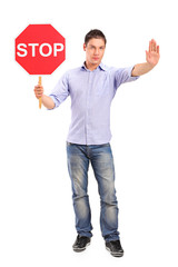 Full length portrait of a man gesturing and holding a traffic si