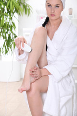 Woman using epilator in bathroom