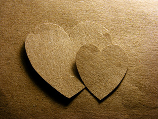 Two paper hearts over paper sheet