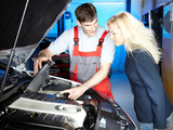 Motor mechanic shows his customer the details of an engine bay