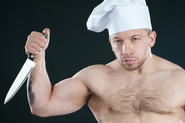 Studio shot of bare torso chef with a kitchen knife