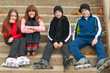 Group of happy teenagers in roller skates sitting on the stairs