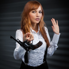 girl with red hair gives a revolver
