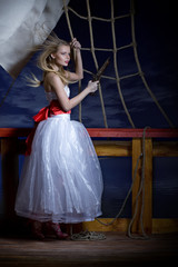Beautiful girl in a white dress on a deck of the sailing ship.