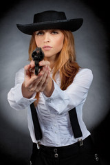 Beautiful girl in hat, red hair, with revolver in hands.