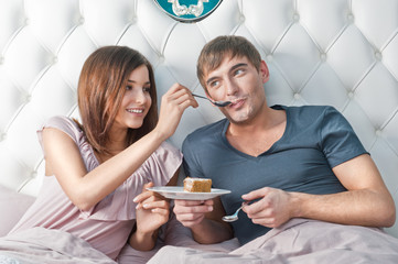 Young lively couple eating cake in their bed