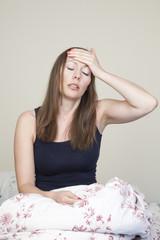 Mit Migräne im Bett sitzend