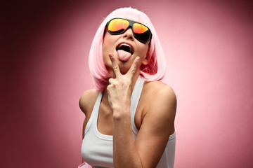 Young girl in pink wig posing on a pink background