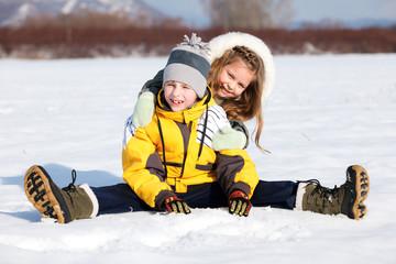 Happy children sit down in the snow