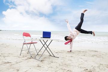 Happy Asian businessman on beach