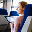 Young woman using her tablet computer while traveling by train