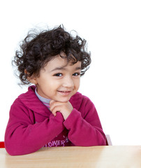 Smiling portrait of a Cute Toddler Girl Sitting at a Desk, Isola