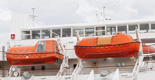 Two orange lifeboats on a ferry