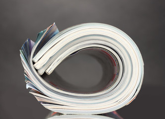 Rolled up magazines on gray background