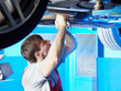 Motor mechanic in garage is working at the underbody of a car