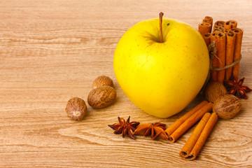 Cinnamon sticks,yellow apple, nutmeg,and anise on wooden table