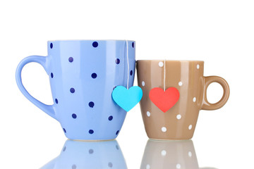 Two cups and tea bags with red and blue heart-shaped label