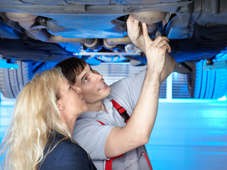 Motor mechanic explaining repair details to a female customer