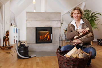 blond lady with firewood in front of a fireplace