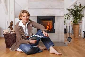 blond lady reading a book in front of a fireplace