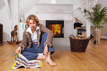blond lady looking at a catalog in front of a fireplace