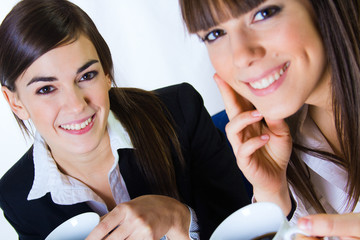 two business women drinking coffee in the office