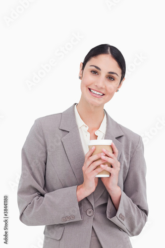Smiling businesswoman holding paper cup