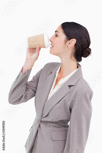 Side view of businesswoman taking a sip out of a paper cup