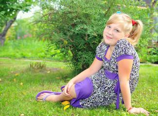 Девочка сидит на лугу