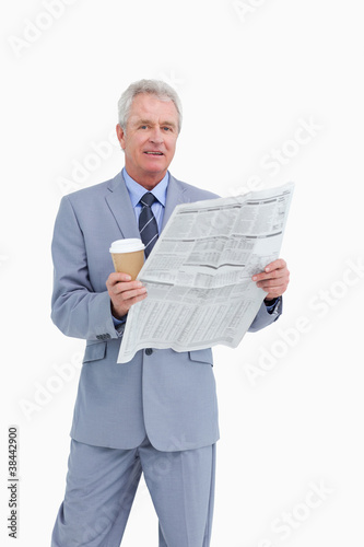 Mature tradesman holding news paper and paper cup