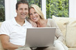 Happy Man & Woman Couple Using Laptop At home