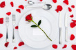 Place setting with red rose and petals